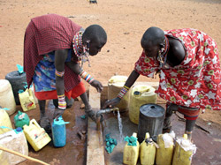 Maasai women fill water jugs, which donkeys will carry to their village, thanks to Lemayian's help.