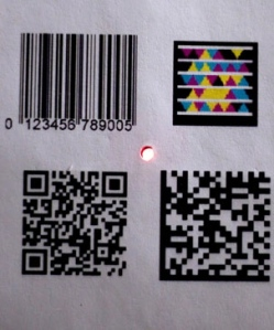 The tiny Bokode device, center, contains far more information than conventional barcodes.