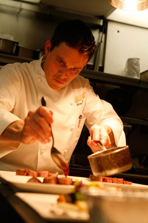 Chef Gavin Kaysen sauces a dish of Magret de Canard at Cafe Boulud in New York. (© Owen Franken).