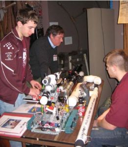 Gloucester High School students CJ Mustone (right) and Brandon Henry (left) describe their engineering projects to Eric Mears '80. Photo: DUE