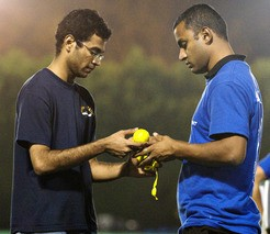 Grad students Srinivasan Jagannathan, left, and Ankur Sinha check the taped tennis balls in preparation for a cricket match at MIT. Tech Photo: Noah Spies.