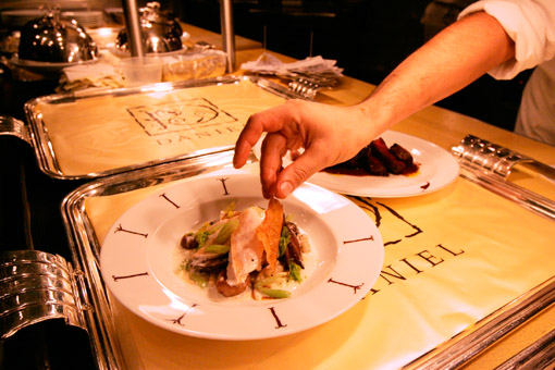 Plating a dish in the kitchen of the French restaurant Daniel, a top eatery in New York
